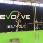 painting Evolve health club sign